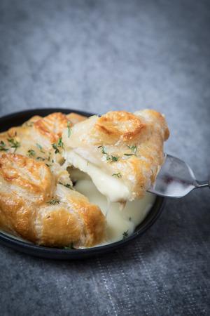 Apéritif en croûte de camembert avec pâte feuilletée et herbes. Tranche de camembert en croûte frite et gluante sur une plaque noire et fond gris. Fromage fondu.