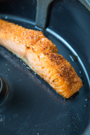 Pan-fried piece of salmon with spices in the fryer. Skin down salmon frying. Close up picture of fried salmon. Dark grey frying pan. Air fryer salmon.