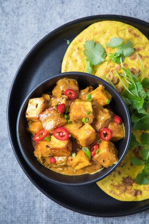 Close up of Indian cheese curry in a dark black bowl with yellow roti and fresh coriander. Paneer Indian balti cottage cheese curry on a grey background.