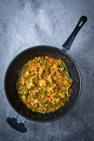 Top view of vegetable korma curry with korma curry paste sauce in a cooking pan. Light grey background. Distant view of Indian korma curry. Stock Photo