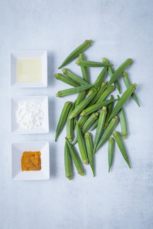 Flour, Indian spices, oil and uncooked raw okra. Uncooked bhindi. Uncooked Indian lady fingers. Healthy Indian bhindi recipe ingredients.