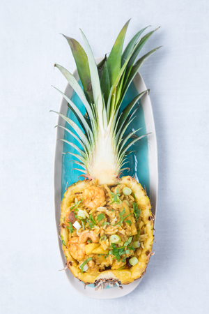 Half of pineapple on a long blue plate with seafood rice and greens. Gourmet stuffed pineapple with seafood fried rice on a white background. 版權商用圖片