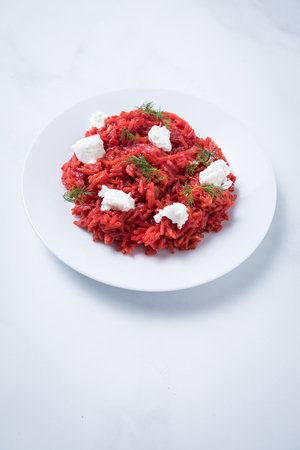 Gourmet creamy red beatroot rice with pieces of white goat cheese and dill on a white round plate and a white background. Elegant beetroot rissotto.