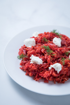 Close up view of gourmet beetroot risotto on a white plate with goat cheese and dill. Cooked red beets rice homemade.