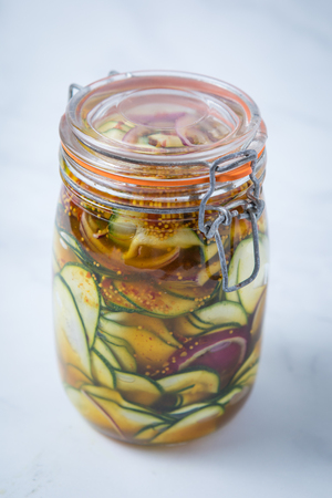 Close up of a spicy courgette red onion pickle marinade in a closed mason jar with a white background. Pickled vegetables in a jar.