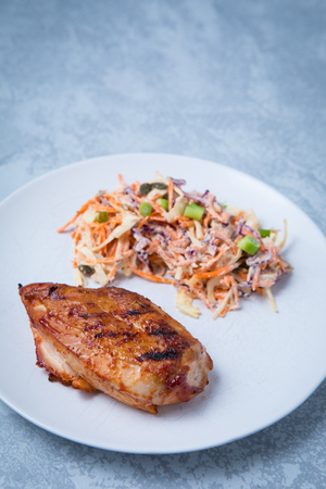 Side view of piece of grilled BBQ chicken breast served with a side grated vegetable salad on a white plate. Grey background. Banque d'images