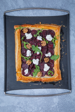 Top view of whole cooked beetroot tart on a black tray and a grey background.