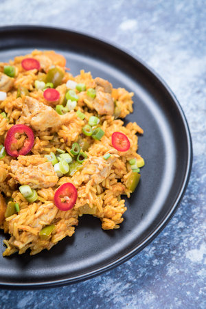 Close up of an African chicken jollof rice dish. Orange spiced African rice with red chillies and chicken on a dark plate and grey background. Stock Photo