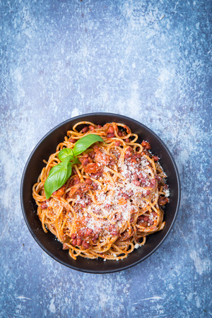 Top view of vegan spaghetti bolognaise or bolognese in a dark black bowl and a ligh grey background. Topped with fresh basil. Stock Photo
