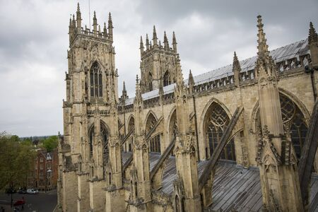 Side view of York Minster Cathedral with gothic and historic cathedral with columns and two towers. Side view on a cloudy day.
