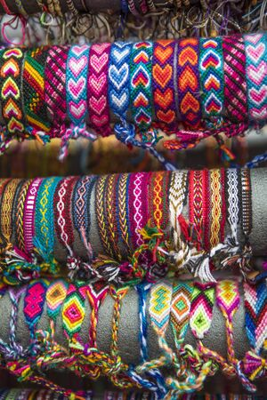 Batch of coloured arm bands in a market. Various patterns. Imagens