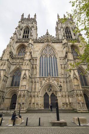 Front view of York Minster Cathedral in England with two large front towers. Cloudy day in England with view of gothic architecture.