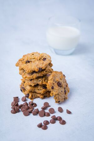 Stack of baked chocolate chip cookies with chocolate chips in the foreground and a glass of milk in the backgorund. Light background.