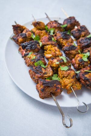 Close up of indian bbq lamb tikka on skewers on a white plate. White background. Stock Photo