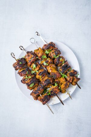 Four lamb tikka bbq skewers charred on a white plate and a white background.