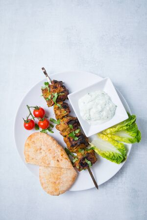 Top view of lamb tikka bbq skewer with fresh parsley, pita bread, tomatoes, lettuce and sauce on a white plate. Light background.