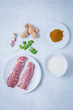 Two raw lamb neck fillets on a white plate with spices, yogurt on white cookware. Fresh ginger, coriander and garlic. Light grey background. Zdjęcie Seryjne