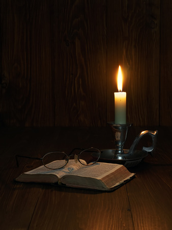 Reading the bible by candlelight photo