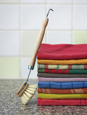 dishwashing: Stack of kitchen towels with dish-washing brush