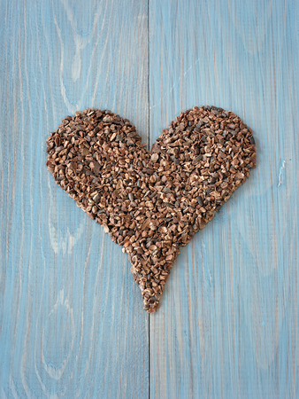 intense flavor: Cacao nibs shaped in heart symbol Stock Photo