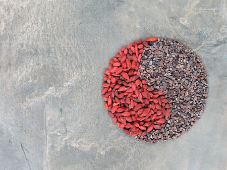 Goji berries and cacao nibs shaped in Yin Yang symbol photo