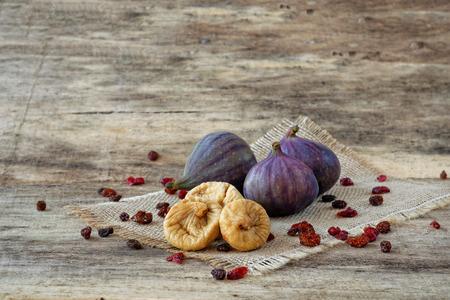 legumbres secas: Higos frescos y secos con las bayas y las pasas de uva en madera