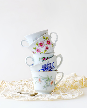 tarde de cafe: Pila de tazas de té de la vendimia para alta té en blanco