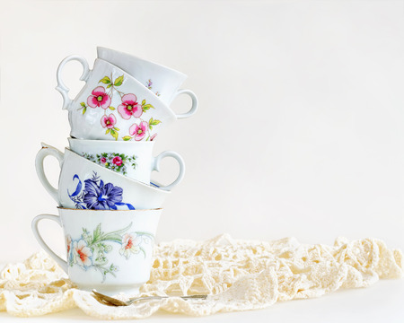 Stack of vintage tea cups for high tea on white Stockfoto