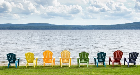 Eight colorful Adirondack chairs lined up on the beach looking out on the lake, mountains and clouds