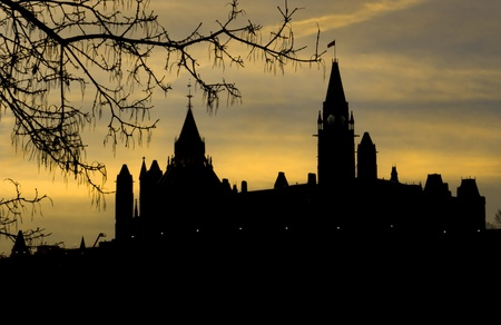 The canadian Parliament bathed in a yellow and blue sunrise glow
