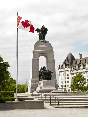 The National War Memorial with Canadian flag and the Fairmont Chateau Laurier in Ottawa, Canada