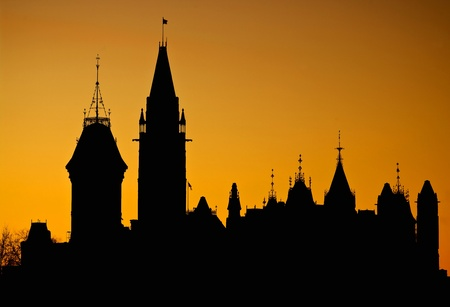 The canadian Parliament silhouette in front of an orange setting sun.