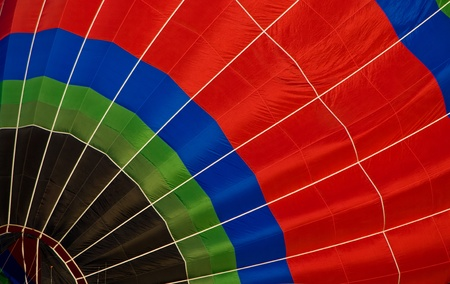 A hot air balloon fills the screen as it is being blown up. photo