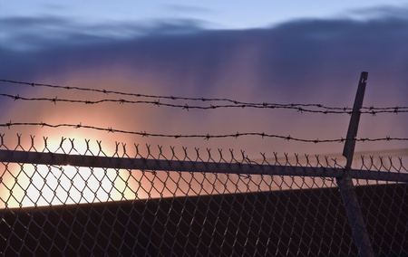 A barb wire fence with sunset in yellow, orange, purple and blue. photo