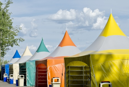 canopy: Five colorful carnival tents against a blue cloudy sky. Stock Photo