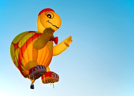A turtle air balloon against a clear blue sky at the festival