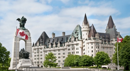 The National War Memorial with Canadian flags and the Fairmont Chateau Laurier Hotel in downtown Ottawa
