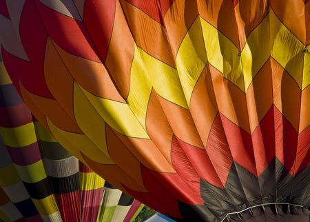 Muli-colored hot air balloons seen closeup while being blown up