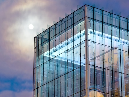 enclosures: A moon looms over a modernist glass building during the twilight hour