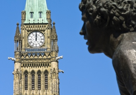 A statue of Terry Fox running in front of the canadian Parliament Centre Block at noon  Reklamní fotografie