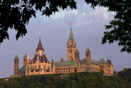 The canadian Parliament in the late day sun framed with green leaves during summer