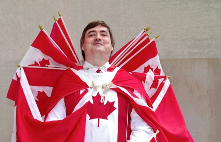 first day: Celebrating Canada Day, a man is dressed with canadian flags  Stock Photo