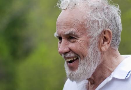 hombre con barba: Un tiro franco de un abuelo sonriente rodeado de zonas verdes