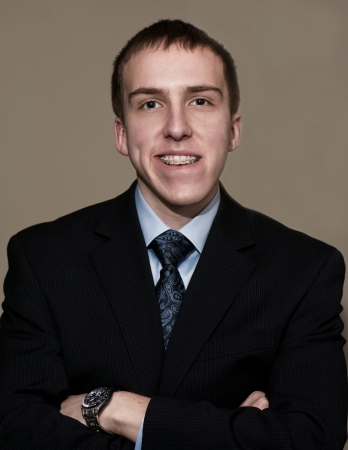 Young business man with braces standing with arms folded