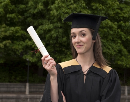 Young woman shows off certificate on graduation day  photo