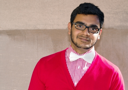 Young asian man with dark rimmed glasses, a white bowtie and red cardigan