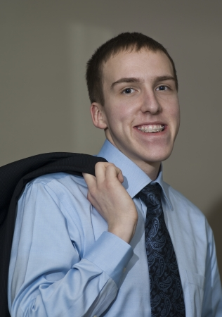 Young business man with braces standing holding suit coat over shoulder