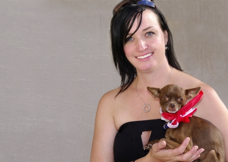 Young woman holding her pet chihuahua wearing a red and white scarf  photo