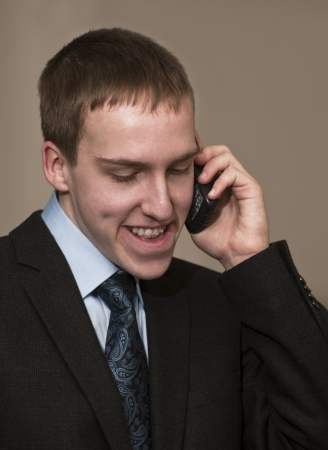 Young business man with braces speaking on cellphone.
