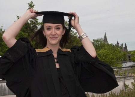 Young woman holding graduation hat on windy day.